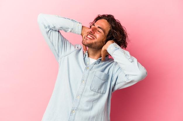 Jonge blanke man geïsoleerd op roze bakcground zelfverzekerd gevoel, met handen achter het hoofd.