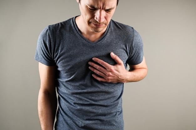 Jonge blanke man grijpt zijn handen voor hart, hartaanval. hartproblemen concept. medisch en farmaceutisch concept. hoge kwaliteit foto