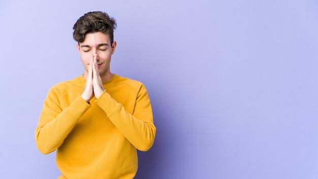 Jonge blanke man hand in hand bidden in de buurt van de mond, voelt zich zelfverzekerd.