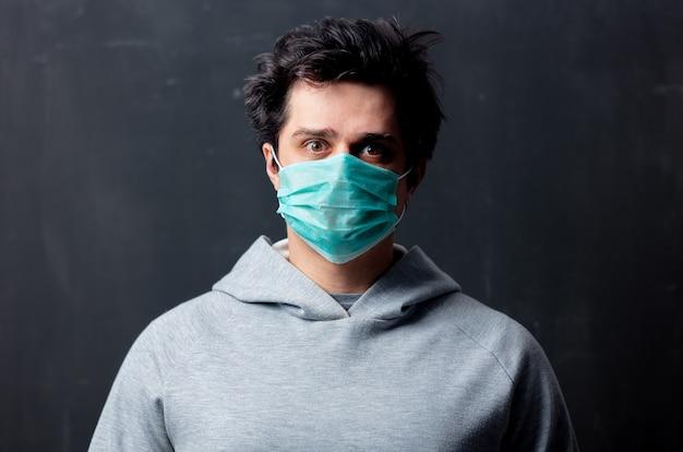 Jonge blanke man in beschermend masker op donkere achtergrond