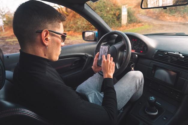 Jonge blanke man in een auto met behulp van een smartphone