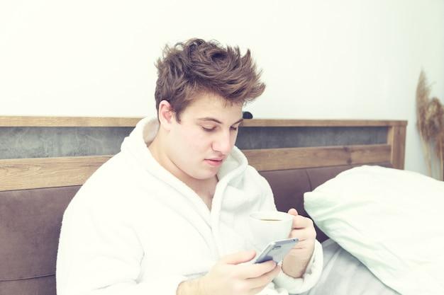 Jonge blanke man in een badjas heeft een kopje koffie en een telefoon. vroeg in bed.
