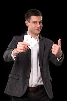 Jonge blanke man in een donker pak en een wit overhemd met twee azen in zijn hand en duim omhoog handgebaar met glimlach op zwarte achtergrond. gokken concept. casino