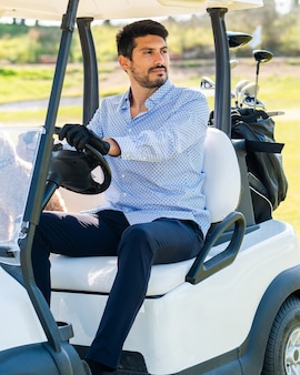 Jonge blanke man in een golfkar met zijn goldendoodle-puppy op een professionele golfbaan