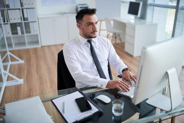 Jonge blanke man in formele shirt en stropdas zitten in kantoor en werken op de computer