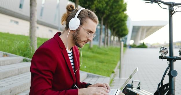 Jonge blanke man in glazen en koptelefoon zittend op stappen buiten, werkt op laptop computer, toetsenbord typen. stijlvolle man werkt op straat als freelancer. elektrische scooter. naar muziek aan het luisteren.