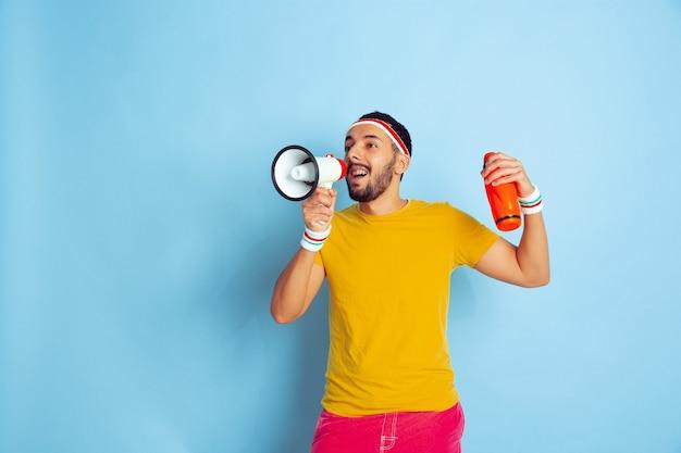 Jonge blanke man in lichte kleren training op blauwe achtergrond concept van sport, menselijke emoties, gezichtsuitdrukking, gezonde levensstijl, jeugd, verkoop. mondvrede roepen, fles vasthouden.