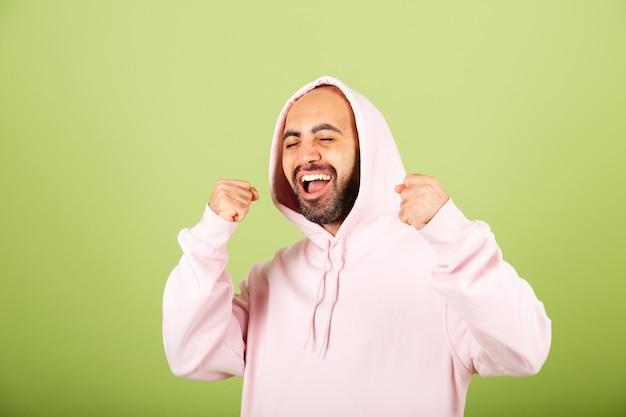 Jonge blanke man in roze hoodie geïsoleerd, gelukkig gebalde vuist met succes van het winnaargebaar