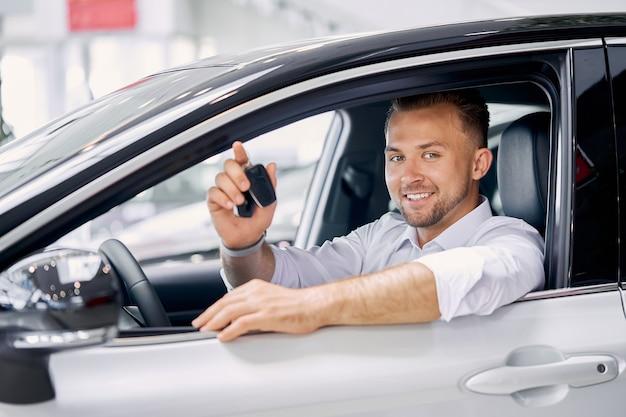 Jonge blanke man is blij om sleutels van auto te krijgen