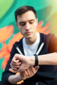 Jonge blanke man is op zijn fitness-armband op veelkleurige achtergrond