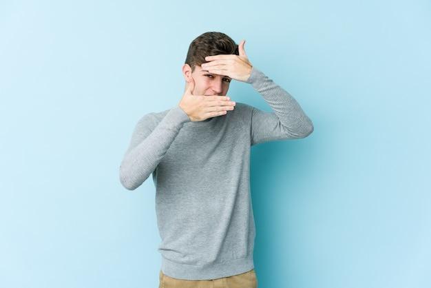 Jonge blanke man knipperen door vingers, beschaamd bedekkend gezicht.