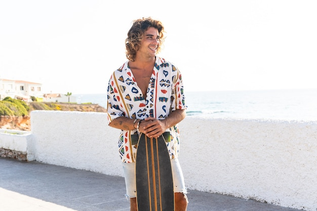 Jonge blanke man longboard oefenen op het strand