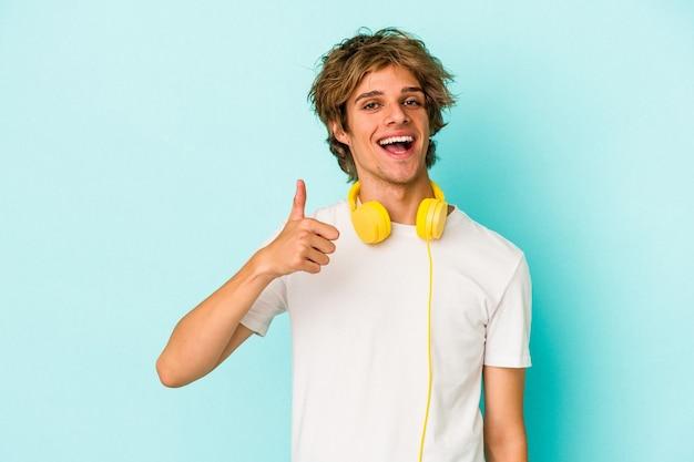 Jonge blanke man luisteren naar muziek geïsoleerd op blauwe achtergrond glimlachend en duim omhoog