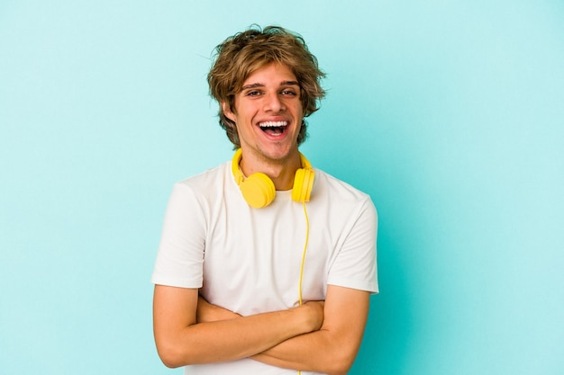 Jonge blanke man luisteren naar muziek geïsoleerd op blauwe achtergrond lachen en plezier hebben.