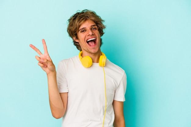 Jonge blanke man luisteren naar muziek geïsoleerd op blauwe achtergrond vrolijk en zorgeloos met een vredessymbool met vingers.