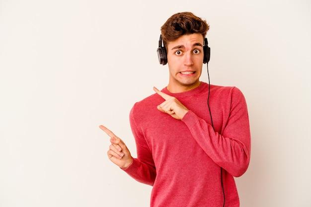 Jonge blanke man luisteren naar muziek geïsoleerd op een witte muur geschokt wijzend met wijsvingers naar een kopie ruimte