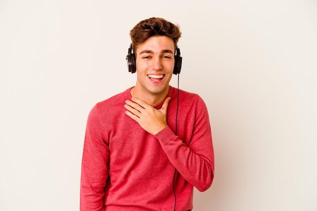 Jonge blanke man luisteren naar muziek geïsoleerd op een witte muur lacht hardop hand op de borst te houden