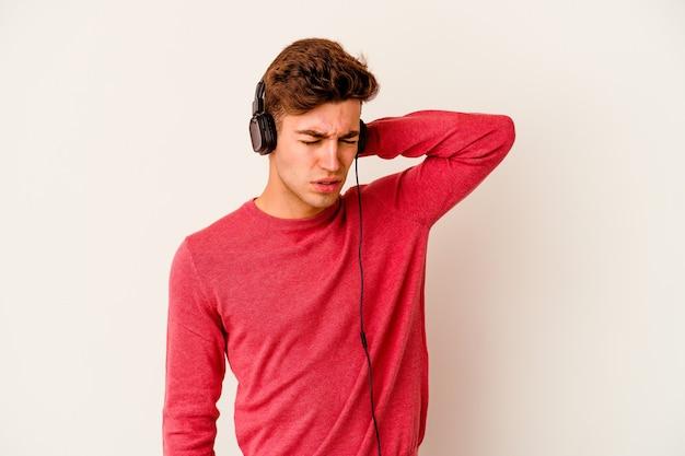 Jonge blanke man luisteren naar muziek geïsoleerd op een witte muur nekpijn lijden als gevolg van een zittende levensstijl