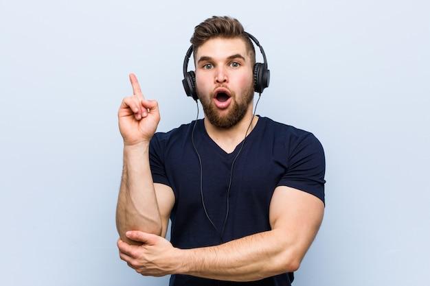 Jonge blanke man luisteren naar muziek met een geweldig idee, concept van creativiteit.
