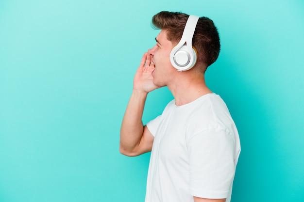 Jonge blanke man luisteren naar muziek met een koptelefoon geïsoleerd op blauwe muur schreeuwen en houden palm in de buurt van geopende mond