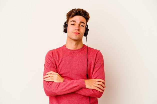 Jonge blanke man luisteren naar muziek op wit die zich zelfverzekerd voelt, de armen over elkaar steken met vastberadenheid.