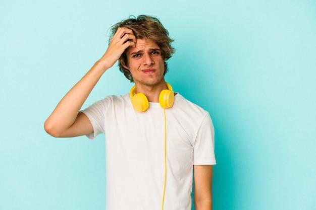 Jonge blanke man luistert naar muziek geïsoleerd op een blauwe achtergrond die geschokt is, ze herinnert zich een belangrijke vergadering.