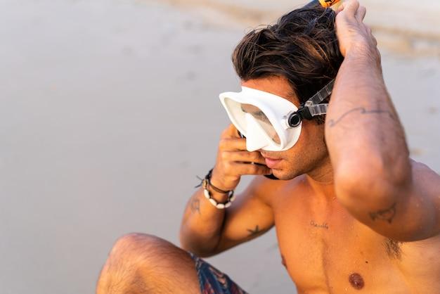 Jonge blanke man maakt zich klaar om de zee in te duiken