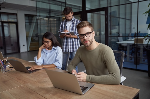 Jonge blanke man mannelijke kantoormedewerker die een laptop gebruikt die aan een bureau zit en naar de camera kijkt