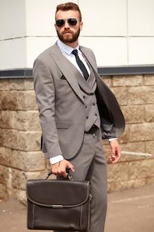 Jonge blanke man met baard in pak naast gebouw na zakelijke bijeenkomst, man in smoking en in zwarte zonnebril buitenshuis. mensen bedrijfsconcept