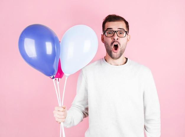 Jonge blanke man met ballonnen met verbaasde uitdrukking en viert een verjaardag