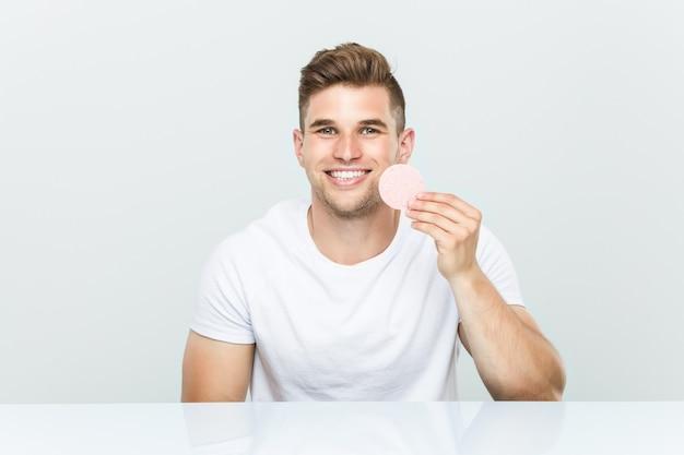 Jonge blanke man met behulp van een gezichtsspons.