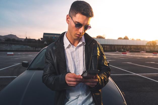 Jonge blanke man met behulp van een smartphone met een sportwagen achter