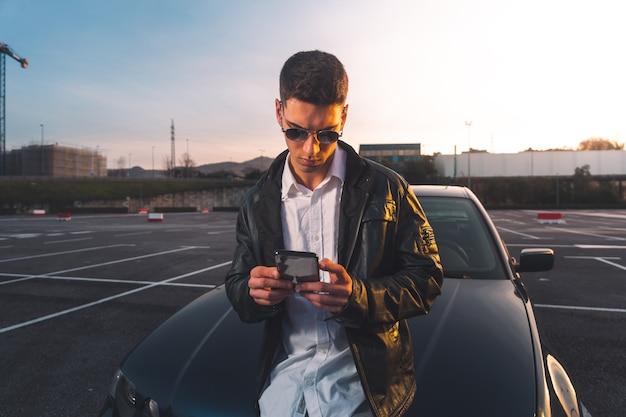 Jonge blanke man met behulp van een smartphone met een sportwagen achter Premium Foto
