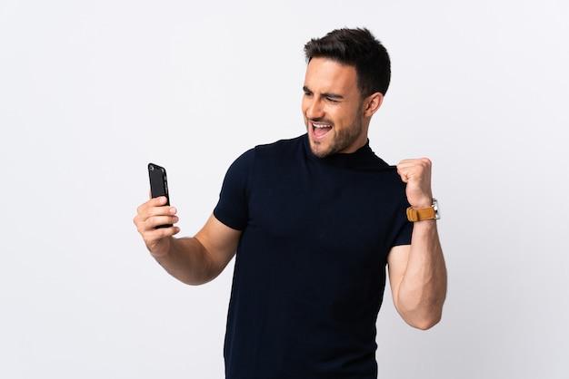 Jonge blanke man met behulp van mobiele telefoon geïsoleerd vieren een overwinning