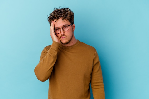 Jonge blanke man met bril geïsoleerd op blauwe achtergrond moe en erg slaperig hand op het hoofd houden.