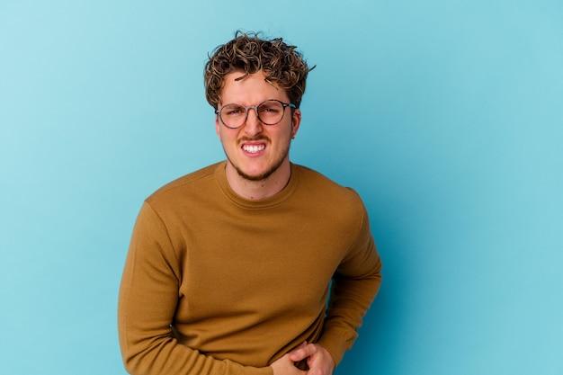 Jonge blanke man met bril geïsoleerd op blauwe muur met een leverpijn, buikpijn