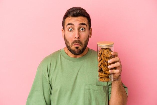 Jonge blanke man met cookies pot geïsoleerd op roze achtergrond haalt schouders op en open ogen verward.