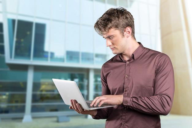 Jonge blanke man met draagbare pc in zijn handen