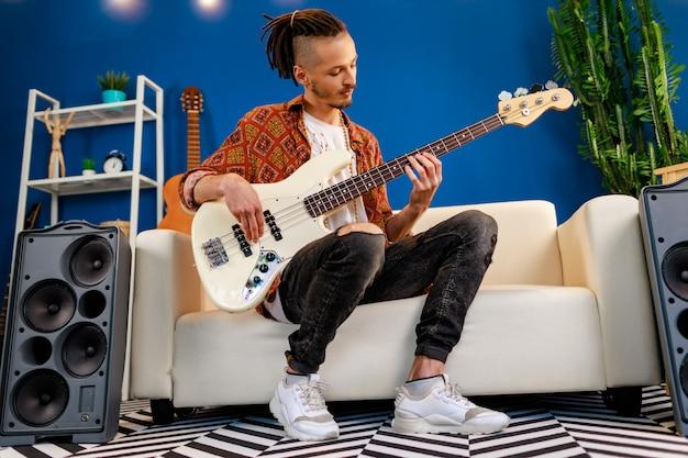 Jonge blanke man met dreadlocks elektrische gitaar spelen in zijn kamer