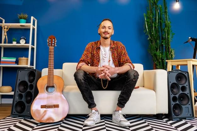 Jonge blanke man met dreadlocks zittend op de bank in de woonkamer in de buurt van gitaar