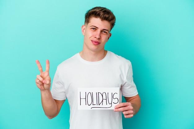 Jonge blanke man met een aanplakbiljet vakantie geïsoleerd op blauwe muur