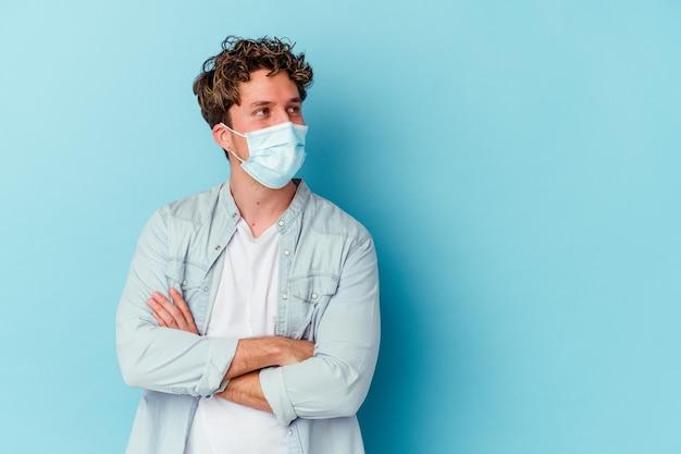Jonge blanke man met een antiviraal masker geïsoleerd op blauwe muur glimlachend zelfverzekerd met gekruiste armen