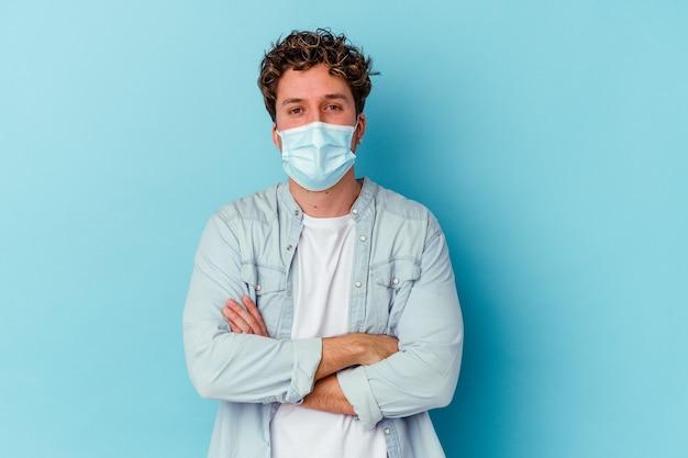 Jonge blanke man met een antiviraal masker geïsoleerd op een blauwe muur die zich zelfverzekerd voelt en vastberaden de armen kruist.