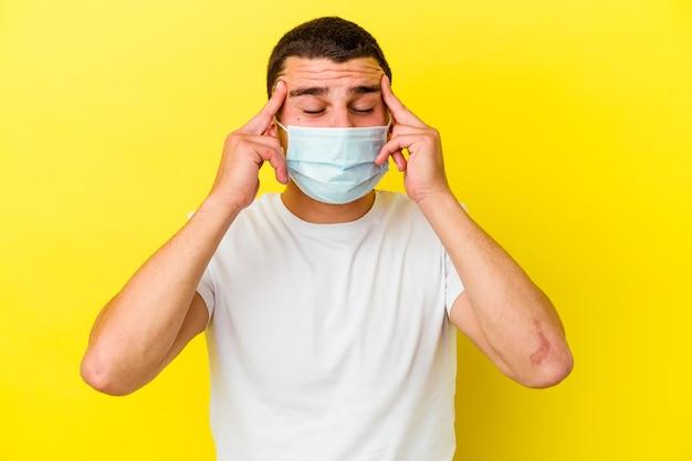 Jonge blanke man met een bescherming tegen coronavirus geïsoleerd op gele muur tempels aanraken en hoofdpijn hebben.