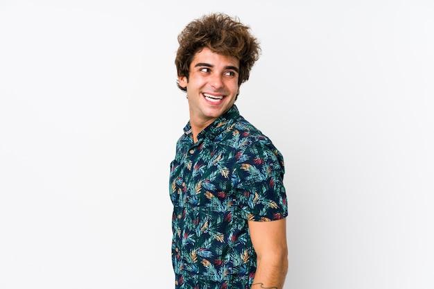 Jonge blanke man met een bloem t-shirt geïsoleerd kijkt opzij glimlachend, vrolijk en aangenaam.