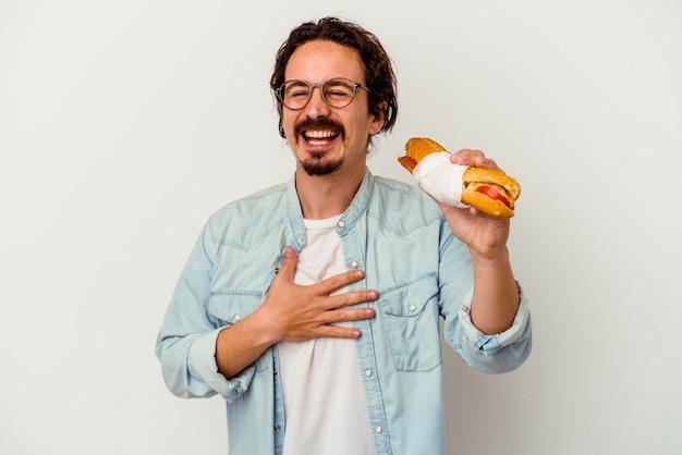 Jonge blanke man met een broodje geïsoleerd op een witte achtergrond lacht hardop hand op de borst te houden.