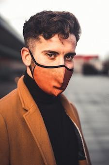 Jonge blanke man met een bruin masker met een bruine jas op straat