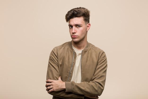 Jonge blanke man met een bruine jas ongelukkig kijken in de camera met sarcastische uitdrukking.