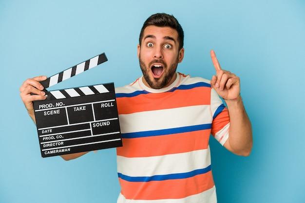 Jonge blanke man met een filmklapper geïsoleerd op blauwe achtergrond met een idee, inspiratie concept.