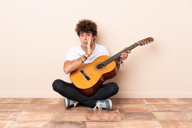 Jonge blanke man met een gitaar zittend op de vloer iets fluisteren